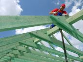 image of purlin  - Carpenter driving a nail into house rafter framing beam - JPG