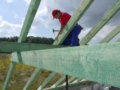 foto of purlin  - Carpenter driving a nail into house rafter framing beam - JPG