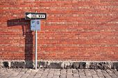 stock photo of traffic signal  - one way sign against brick wall - JPG
