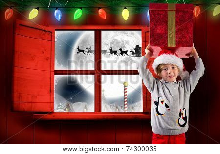 Festive boy holding a gift against santa delivery presents to village