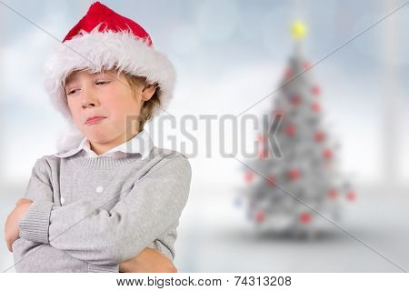 Festive boy sulking against blurry christmas tree in room