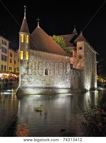 Old fortress-prison on the island in the middle of the river. Castle illuminated by spotlights and is beautifully reflected in the dark water. In the river white swans float.