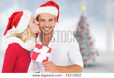 Young festive couple against blurry christmas tree in room