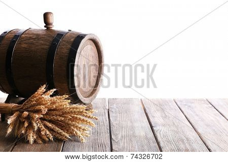 Old barrel with wheat on table on white background