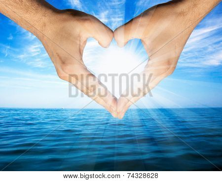 Hand forming heart shape in front of blue water of ocean and sunny sky
