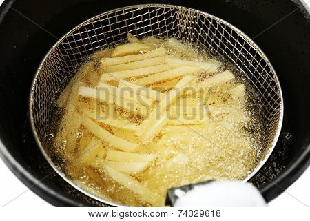 French fries in deep fryer, closeup
