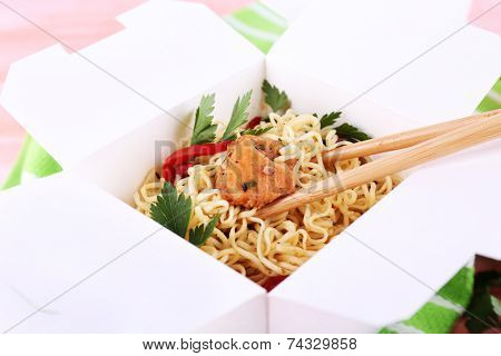 Chinese noodles and sticks in takeaway box on green napkin on pink background