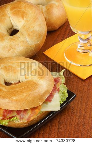 Bagel With Bacon, Cheese And Lettuce And Orange Juice