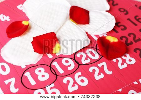 Sanitary pads and rose petals on calendar background