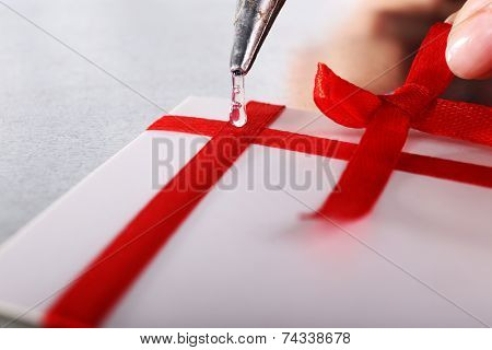 Woman's hand decorating card with red ribbon and bow with a help of glue gun