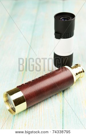 Modern monoculars on wooden background