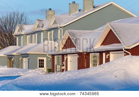 Rowhouses with piles of snow after a snow storm.
