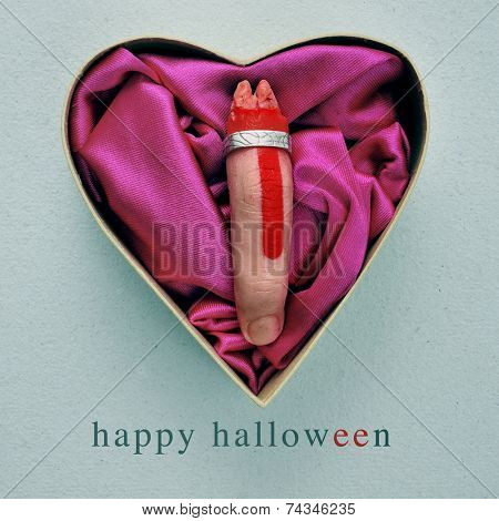 a scary amputated finger with a ring in a heart-shaped gift box, and the text happy halloween