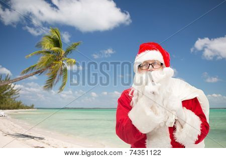 christmas, holidays, travel and people concept - man in costume of santa claus with bag making hush gesture over tropical beach background