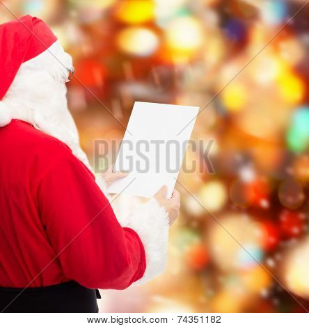 christmas, holidays and people concept - man in costume of santa claus reading letter over red lights background