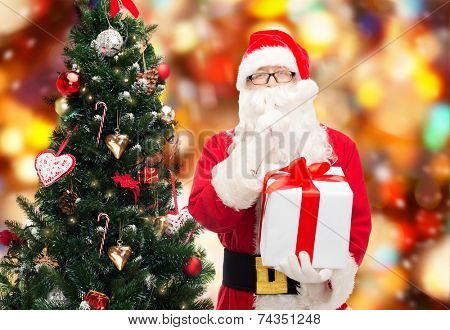 christmas, holidays and people concept - man in costume of santa claus with gift box and tree making hush gesture over red lights background