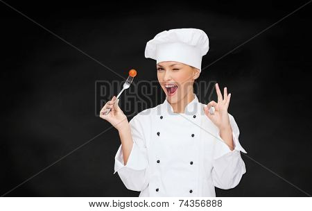 cooking and food concept - smiling female chef, cook or baker with fork and tomato showing ok sign