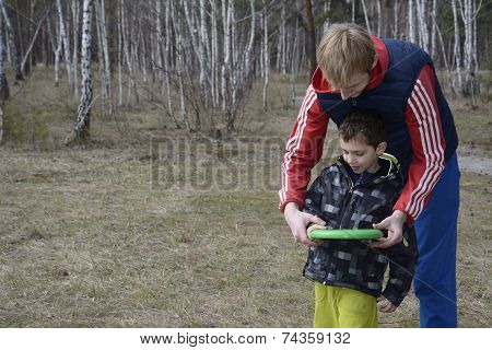Spring In The Forest On A Glade Father Teaches His Son To Throw The Disc.