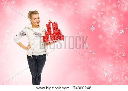 Young smiling girl with gift boxes on winter background
