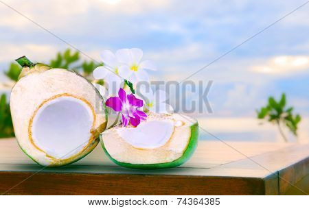 Twon Half Of Green Coconut Water On Top  Wood Table With Tropical Orchid Flowers And White  Frangipa