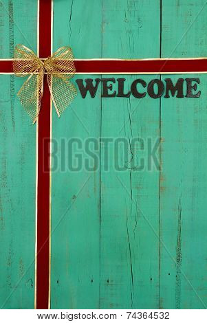 Antique green welcome sign with red and gold velvet ribbon Christmas background