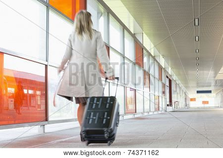 Full length rear view of young businesswoman with luggage rushing in railroad station