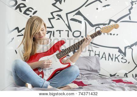 Full-length of teenage girl playing guitar in bedroom