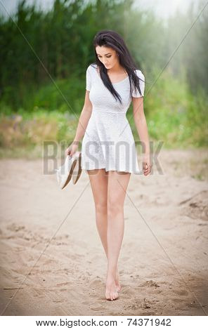 Attractive brunette girl with short white dress strolling barefoot on the countryside