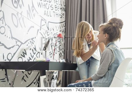 Teenage girl putting lipstick on sister at home