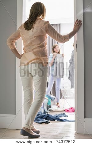 Full-length rear view of mother watching daughters trying on clothes in room