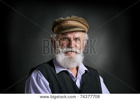 Old  man in cap on black background