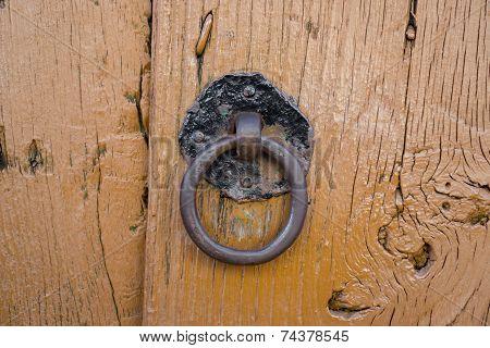 Front view of old doorknocker and orange painted wooden door