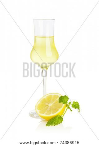 Glass of Limoncello liqueur with half lemon and mint leaf isolated on white background