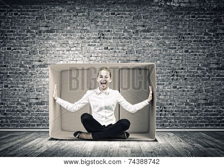 Young emotional woman trapped in carton box