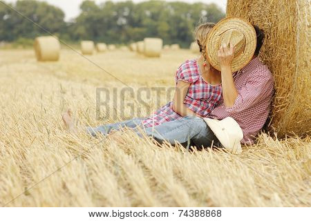 In Love Young Couple On Haystacks In Cowboy Hats