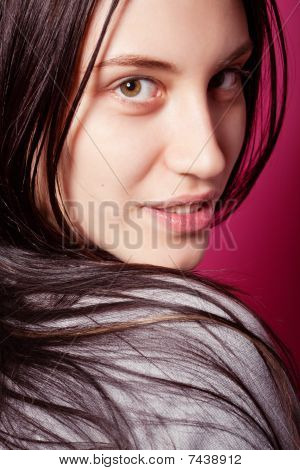 Portrait Of Attractive Brunette Girl With Long Hair Over Pink