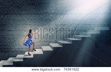 Young woman in blue dress walking on ladder