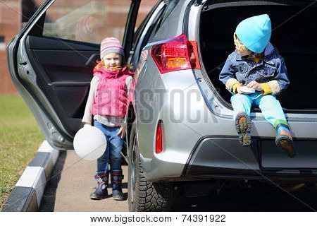 Little boy in yellow glasses sitting in open trunk of foreign car and girl with white balloon standing at the open door