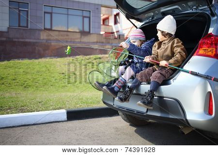 Two children are sitting in open trunk with fishing rod and net