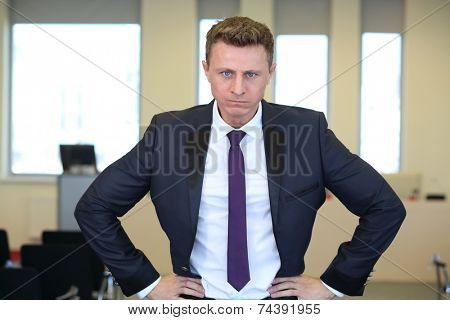 Portrait of young angry businessman with hands on hips in the office