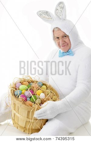 A senior adult man in an Easter bunny outfit happily showing off a bushel of colorful eggs.  On a white background.