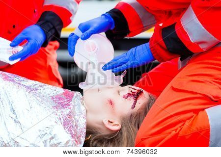 Emergency doctor and nurse or ambulance team giving oxygen to accident victim