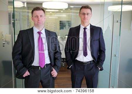 Two solid businessmen in suit standing at entrance to conference hall