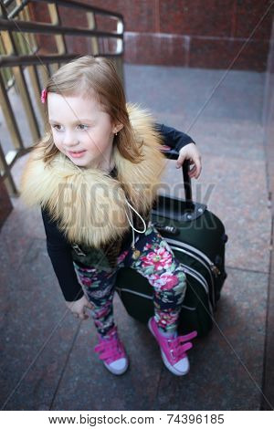 Happy little girl standing with a large green suitcase on stairs
