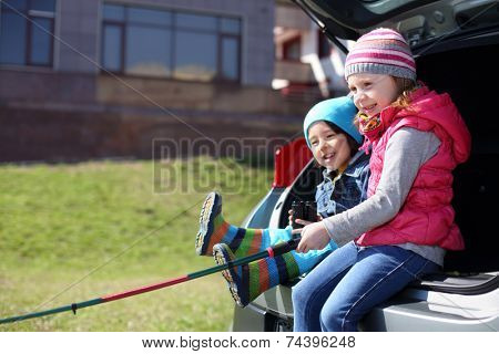 Little boy and girl with fishing rod playing in open trunk of foreign car