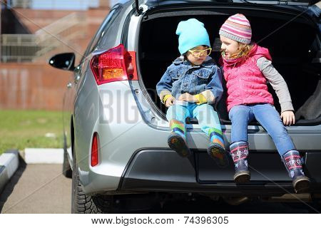 Little boy in yellow glasses and girl sitting in open trunk of foreign car