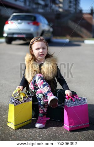 Little girl sitting on suitcase with her legs crossed with colored gift bags in middle of road