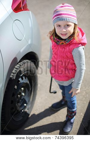 Portrait of a little girl in pink waistcoat and striped hat with socket wrench in hands near car