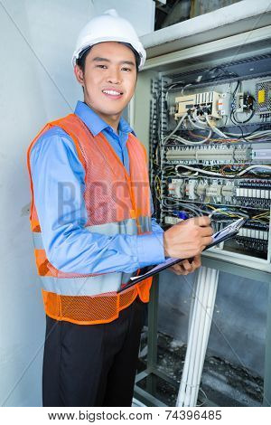 Asian Indonesian Technician or electrician making function test on breaker box or switch box with power lines on construction site or in factory for acceptance