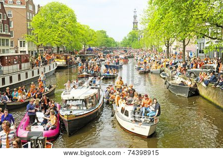 AMSTERDAM - APRIL 26: Amsterdam canals full of boats and people in orange during the celebration of kings day on April 26, 2014 in Amsterdam, The Netherlands